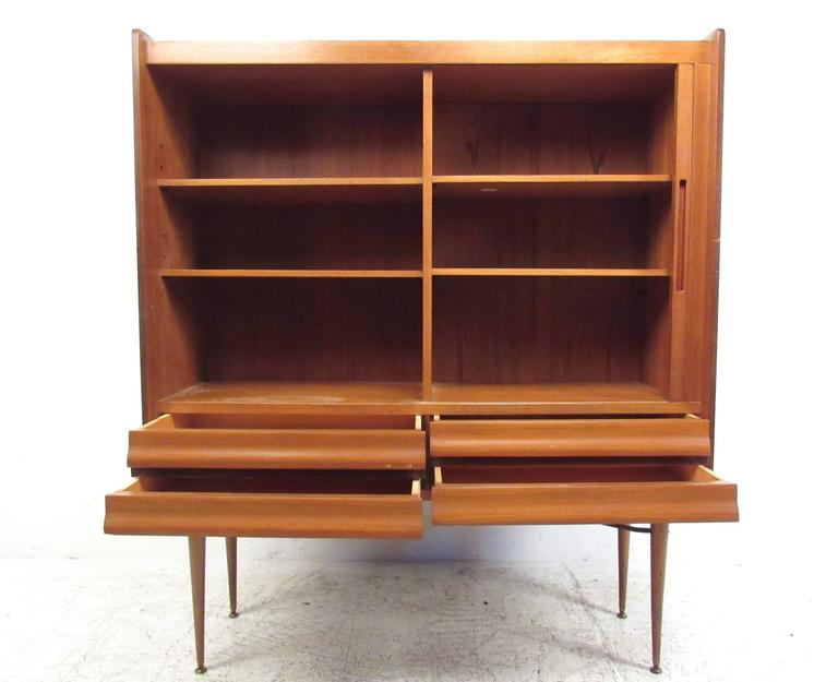 This tall vintage cabinet features unique Scandinavian style with plenty of storage in side-by-side arrangement. Mixed wood design combines mahogany, teak, and rosewood for a beautiful end product. Open shelves for display are paired with a stylish