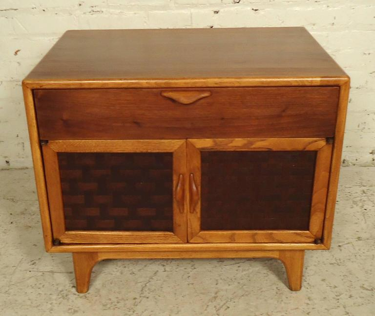 Elegant Mid-Century side table features a top drawer, bottom storage compartment and set of basket woven front doors on sturdy legs. Attractive oak and walnut accenting, as well as sculpted handles to add flair.