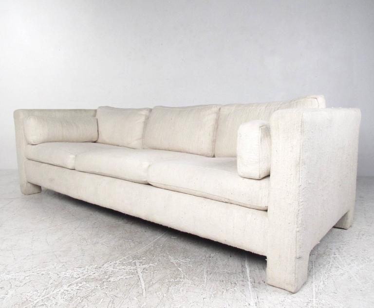 This comfortable modern sofa features the Mid-Century design of Milo Baughman as manufactured for Thayer Coggin. Subtle lines and comfortable proportions make this vintage sofa an excellent addition to any seating arrangement. Please confirm item