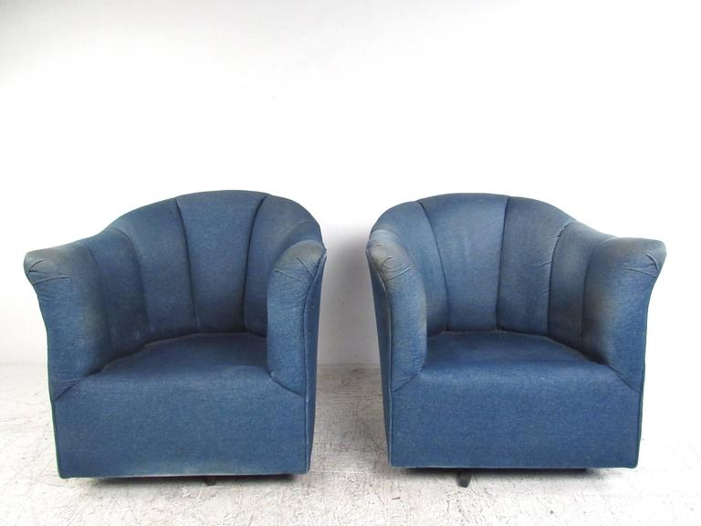 This comfortably upholstered pair of chairs features denim covering, comfortable overstuffed cushioning, and swivel bases. Unique and comfortable pair of chairs suitable for any modern or contemporary setting. Please confirm item location (NY or NJ).