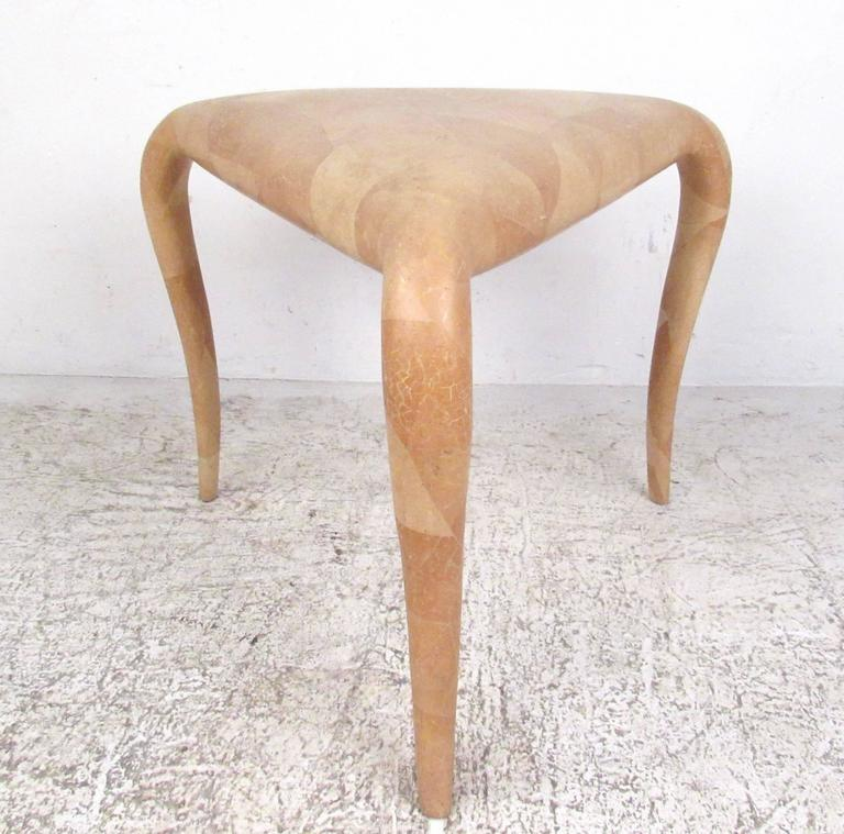 This beautiful sculpted end table by R & Y Augousti of London makes a uniquely shaped triangular table for various settings. Manufactured in Mid-Century France, it features a tessellated bone veneer with a patchwork style design. Truly impressive