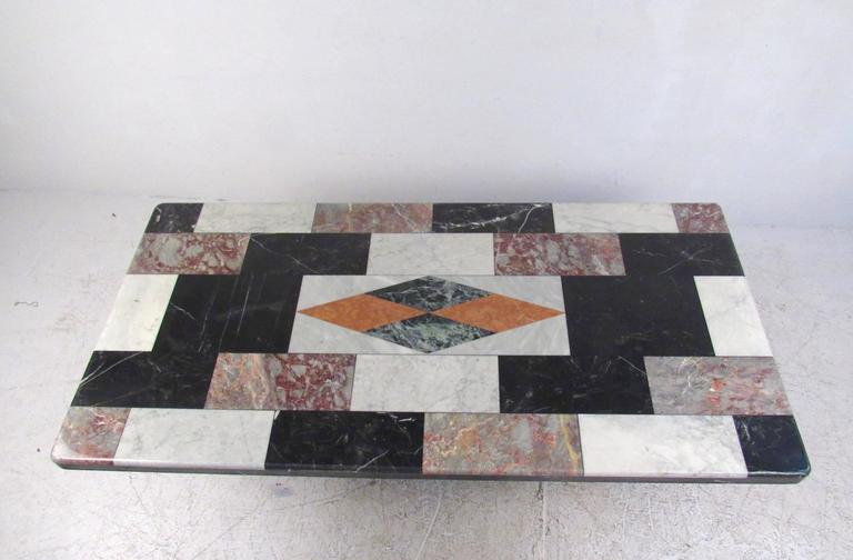 This stunning vintage Italian marble-top table features unique mixed marble top with decorative geometric inlay. Sturdy pedestal design allows for plenty of leg room underneath, while the unique multicolored top adds impressive Mid-Century style to