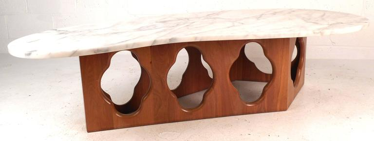 This beautiful vintage Modern kidney shaped coffee table features a sculpted teak wood base with intricate cut out designs and stylish white marble top. The unique shape of the base makes it an impressive addition to any modern interior. Please