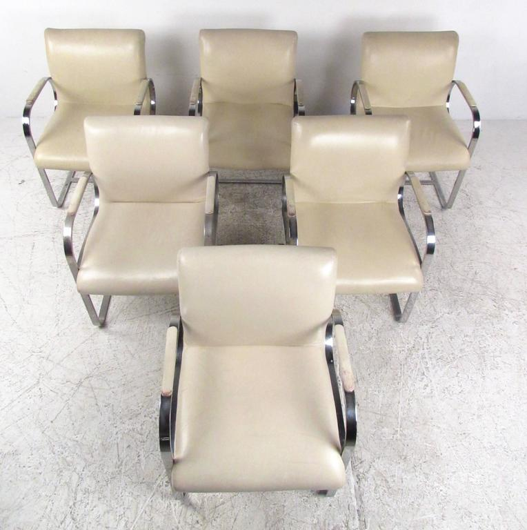 This high quality set of vintage leather and chrome dining chairs features very heavy chrome construction and stylish cantilever design. The matching set boasts an impressive design similar to Mies van der Rohe Brno style chairs, but with an even