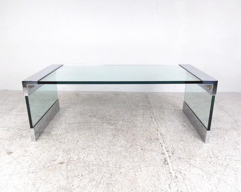 This uniquely angular coffee table features impressive Mid-Century style with quality chrome and glass construction. Thick glass top and sled legs are protected and accented by heavy chrome fittings. Similar in style to the popular Pace designed