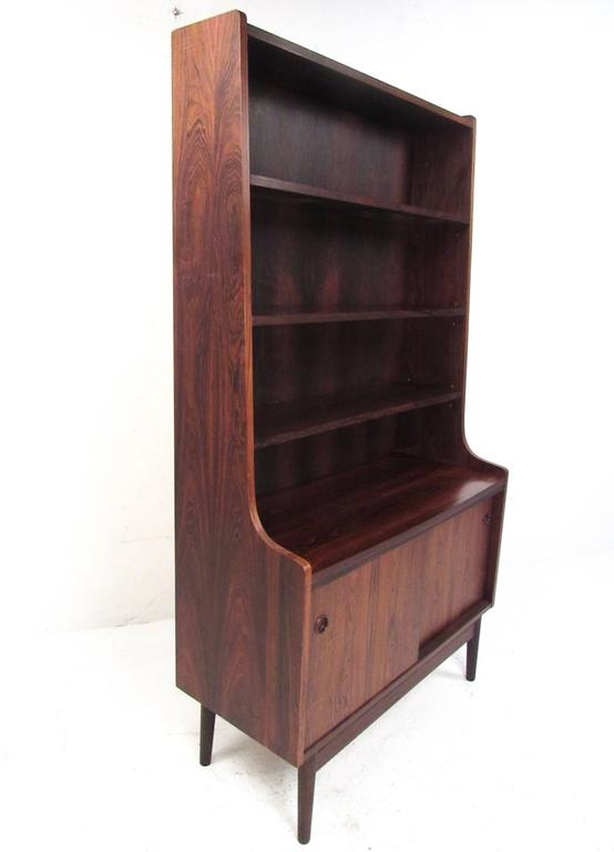This stunning vintage rosewood secretary desk features carved cabinet handles, a pull-out work surface, plenty of display shelves, and a sliding cabinet for added storage. Beautiful Mid-Century Modern rosewood finish makes a great addition to any