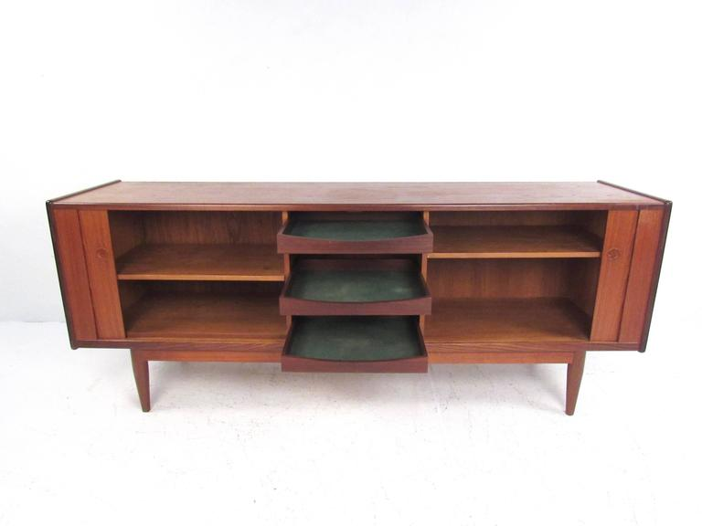 """This vintage teak sideboard features a tambour design similar to that of Hans Wegner's """"the Presidential"""" sideboard. Tapered legs, carved door pulls, and plenty of storage space make this a fantastic addition to any dining room set. Felt"""