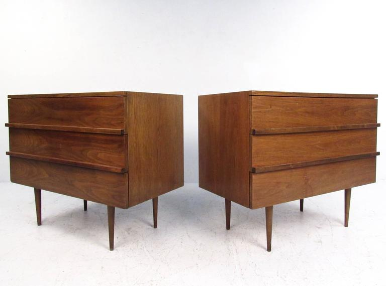 This pair of vintage modern walnut dressers make an excellent addition to any interior in need of stylish storage. Thin and tall tapered legs offset the wide design and robust walnut finish. Carved drawer pulls and plenty of storage space make these