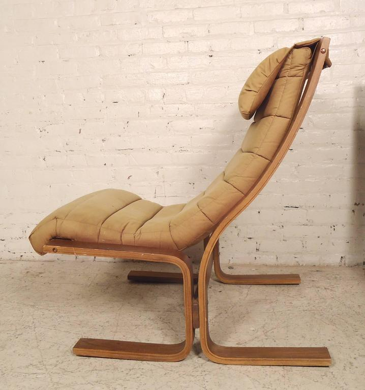 Lovely Danish modern style lounge chairs with bentwood frames and loose cushioning including headrest. These Eames era chairs show great design with comfortable aesthetic.