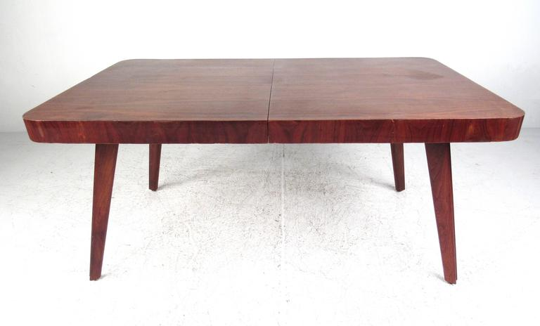 This uniquely sized vintage dining table comes matched with a set of six vintage dining chairs. Wonderful Mid-Century design exemplified with the stunning sculpted legs shared by both table and chairs. Comfortable seats for dining room use, perfect