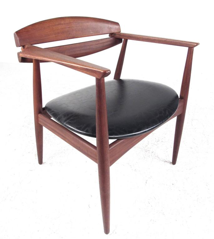 This vintage modern dining chair features unique sculpted seat back and arm rests with vinyl covering and tapered legs. Stunning shape and comfortable design make this Mid-Century Modern an excellent choice for home, office, or occasional seating.