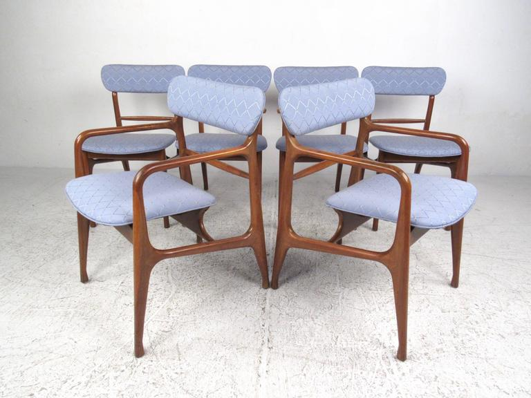 This beautiful sculpted dining set features six matching dining chairs paired with a circular dining table presented with two leaves. The elegance of the sculpted walnut frames with flowing lines and floating seats are wonderfully complimented by