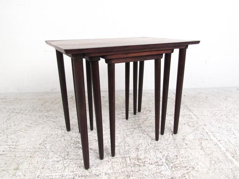 This set of three elegant vintage nesting tables features rich Mid-Century rosewood finish, tall tapered legs, and stylish lines. Manufactured by Bramin in Denmark, circa 1960s, this beautiful set makes a versatile addition to home or office. Please