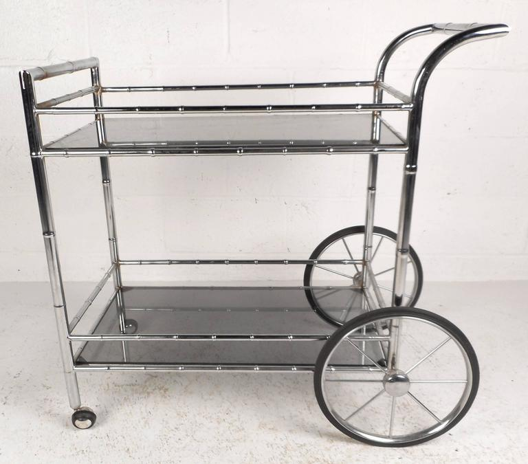 Sleek vintage modern bar cart with a faux bamboo chrome frame, large spoked wheels, and smoked glass shelves. The gorgeous two-tier design features extra stretchers to prevent items from falling off while in motion. Perfect for use as a serving