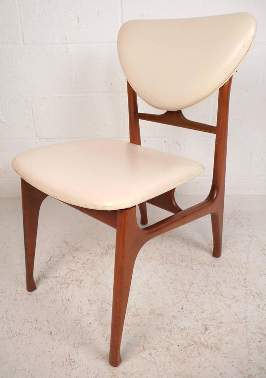 Stunning set of four Mid-Century Modern dining chairs feature a vintage teak finish and a unique sculpted frame. The stylish floating seat and shapely backrest provide optimal comfort. The beautiful white vinyl upholstery is sure to add style to any