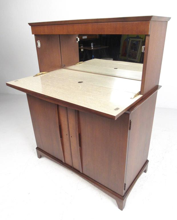 This stylish compact dry bar features an impressive array of cabinet space for optimal barware storage in any setting. Drop front mirrored back cabinet provides ample workspace and room for liquor storage, while lower cabinet features glass and