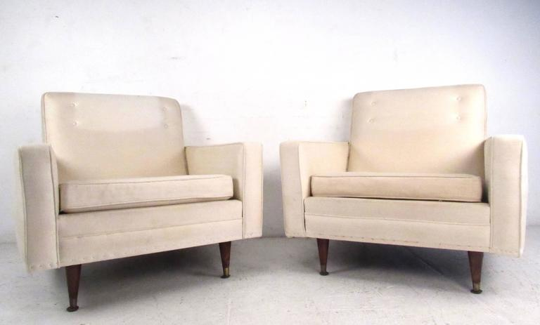 This pair of Mid-Century Modern lounge chairs feature the simplistic modern style of the 1960s and 1970s, with spacious comfortable seats, tapered legs, and brass feet. Button tufted seat backs and ample padding add to the appeal of this vintage