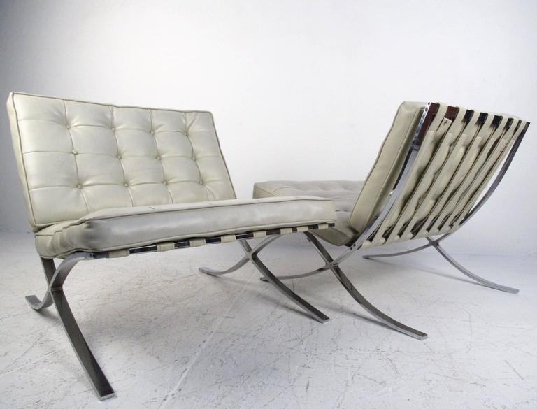 This pair of vintage lounge chairs features wide tufted vinyl seats, strap seat webbing and sleek/stylish chrome frames. This stylish mid-century pair is inspired by the iconic style of Mies van der Rohe and make a comfortable addition to any