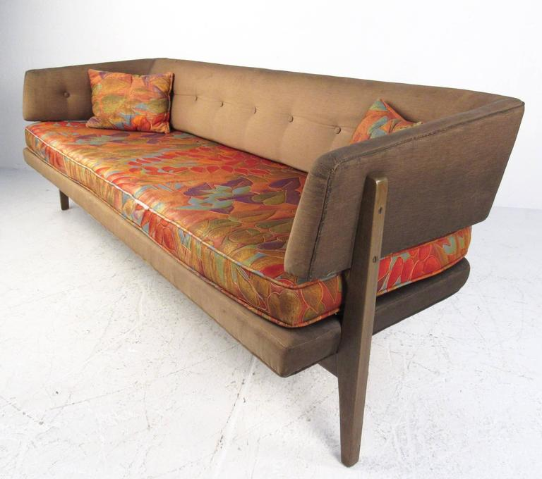 This stunning vintage sofa by Edward Wormley for Dunbar features a tufted sculptural seat back with unique tapered walnut legs. Uniquely covered vintage throw pillows match the two tone upholstery of the sofa, whose modern lines and comfortable