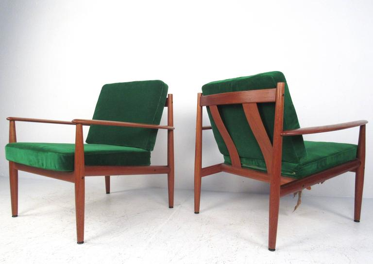 This vintage pair of teak armchairs features unique sculpted frames designed by Grete Jalk for France and Son. Plush green microsuede/velour-like upholstery over spring style seats make this pair of the perfect mix of comfort and style. Original