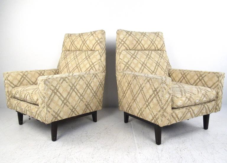 This pair of 1950s high back lounge chairs by Edward Wormley for Dunbar features iconic Mid-Century design and comfortably sculpted seat backs. Spacious seats with plush vintage fabric make these an ideal pair of modern chairs for any setting.