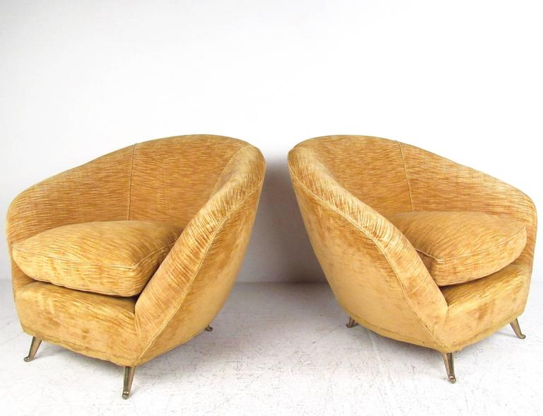 This unique pair of stylish sculptural lounge chairs feature Mid-Century Italian design in plush velvet upholstery. Angled brass legs, plush and well-padded upholstery, and comfortable rounded seat backs make this vintage pair of lounge chairs the