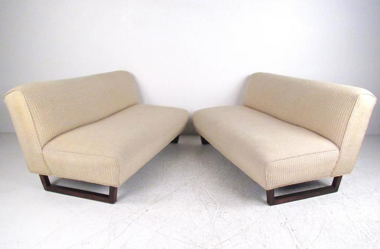 This vintage pair of armless sofas feature unique rosewood sled legs with stripped vintage fabric. Comfortable low seating for any interior, these low profile settees make a stylish seating addition to home or business. Please confirm item location