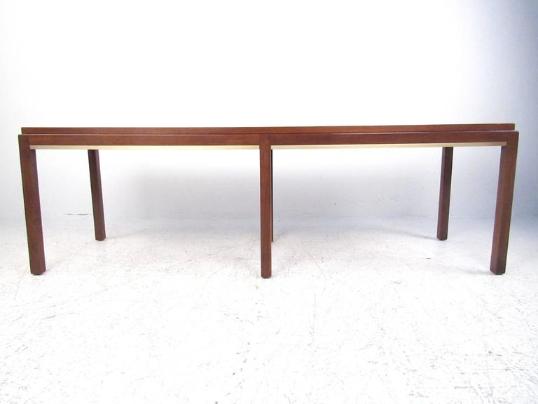 This vintage modern rectangular coffee table features statuesque walnut construction and elegant brass trim. This uniquely tall table features six slender legs for the perfect mix of support and style. Please confirm item location (NY or NJ).