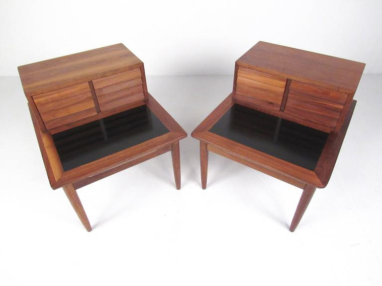 This unique pair of louvered drawer end tables feature stylish walnut frames with painted black tops. Designed with a pair of drawers for added storage, this matching pair of American of Martinsville two tier end tables make these the perfect pair