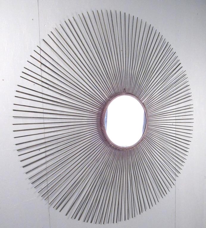 This large starburst mirror features elegant iron spokes around a small centre mirror. This impressive Mid-Century design makes this stellar sunburst design a beautiful addition to any home or office. Please confirm item location (NY or NJ).