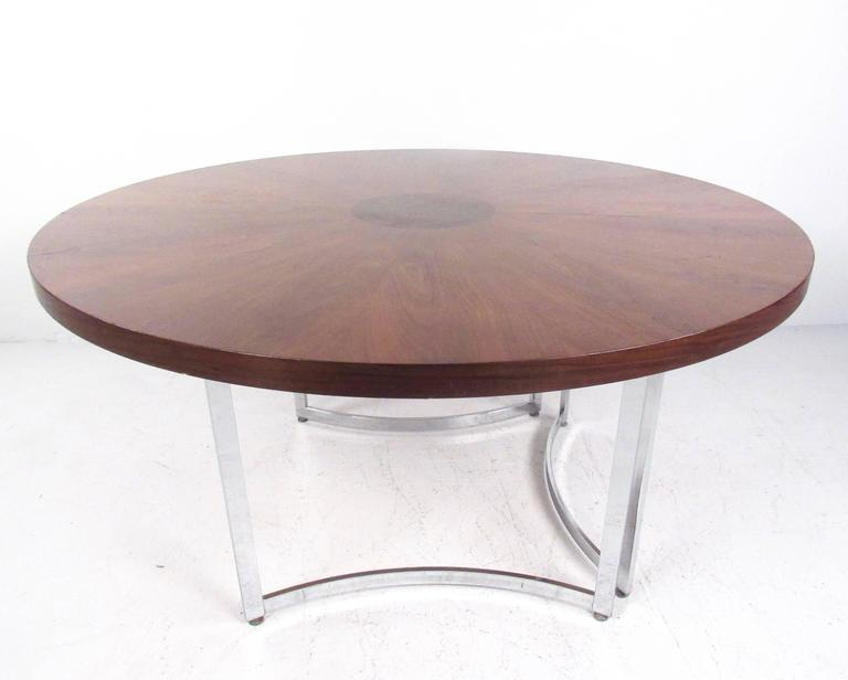 This vintage circular dining table features a beautiful burl wood marquetry top with a stylish sculpted chrome base. The sturdy Mid-Century centre table makes a lovely addition to dining room or kitchen, and offers a spacious round tabletop for