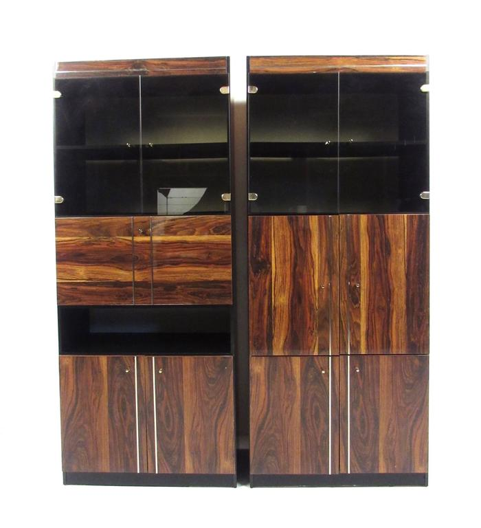 This beautiful pair of contemporary modern cabinets offer a spacious mix of display shelving and interior storage. Matching pair features rosewood style laminate fronts and unique trim, please confirm item location (NY or NJ).