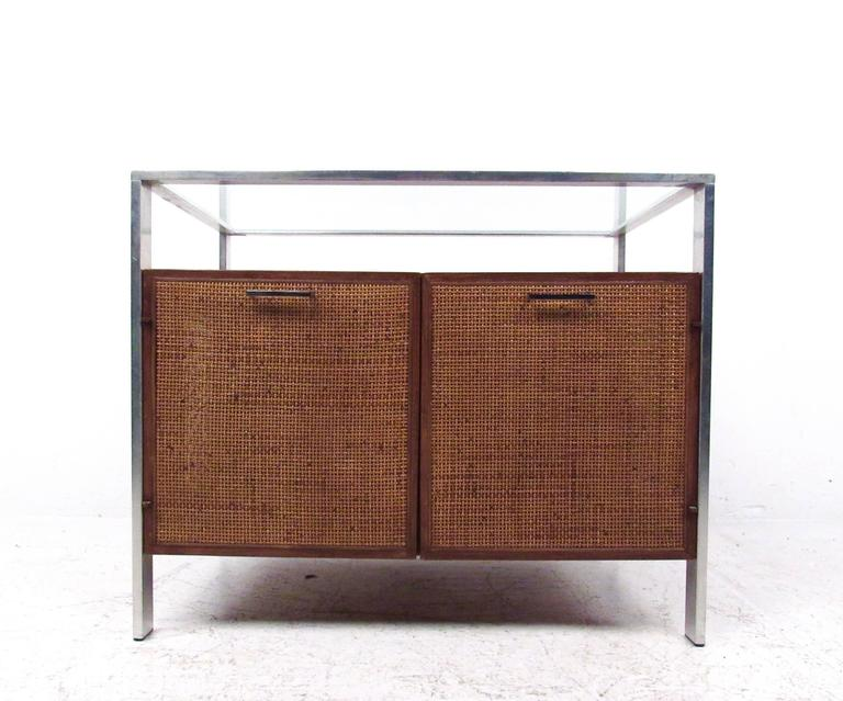 This vintage modern glass top cabinet features woven cane doors and sides with a two-tier top. Chrome finish frame and handles complete the unique Mid-Century Modern appeal of the piece. Perfect option for stylish home or office storage, please