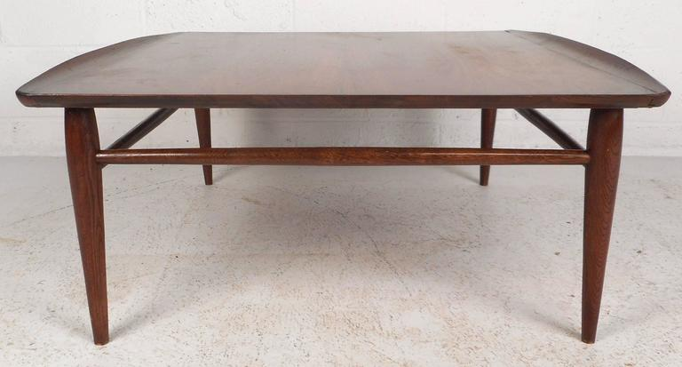 Beautiful vintage modern coffee table features unique raised edges and tapered legs. Sleek design with stretchers between each leg ensuring sturdiness without sacrificing style. The gorgeous walnut wood grain is sure to compliment any modern