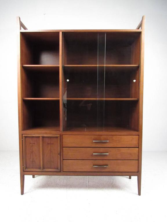 This vintage modern walnut cabinet features spacious storage shelves, lower cabinet and drawers for storage, and a stylish Mid-Century design. Unique drawer pulls and inlaid bowtie details add to it's vintage American charm. Please confirm item