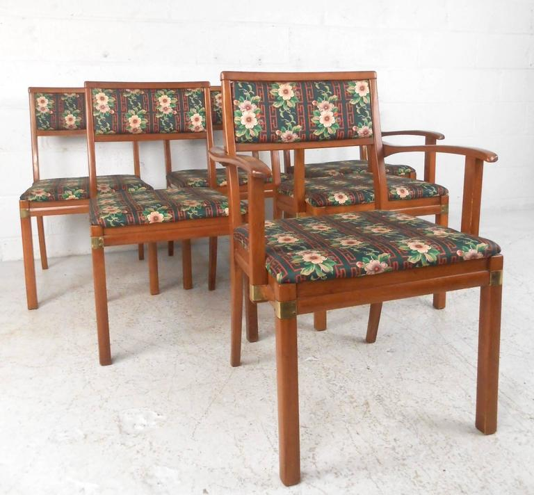 This set of six American dining chairs includes two head chairs with sculpted hardwood arms. Unique brass trim adds some extra Mid-Century appeal to the matching set, while the natural wood finish is offset by vibrant vintage floral covering. Please