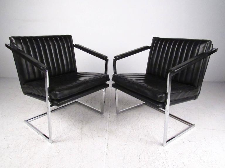 This pair of vintage chrome side chairs features sloped upholstered arms and plush upholstered seats. The stylish modern appeal of this well-crafted pair of arm chairs make this vinyl and heavy chrome set the perfect addition to home office seating.