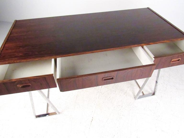 This Mid-Century style Campaign desk features Scandinavian Modern design with chrome finish base and Rosewood veneer desktop. Three drawer design allows for plenty of storage, while the stylish chrome base makes this a unique modern addition to any
