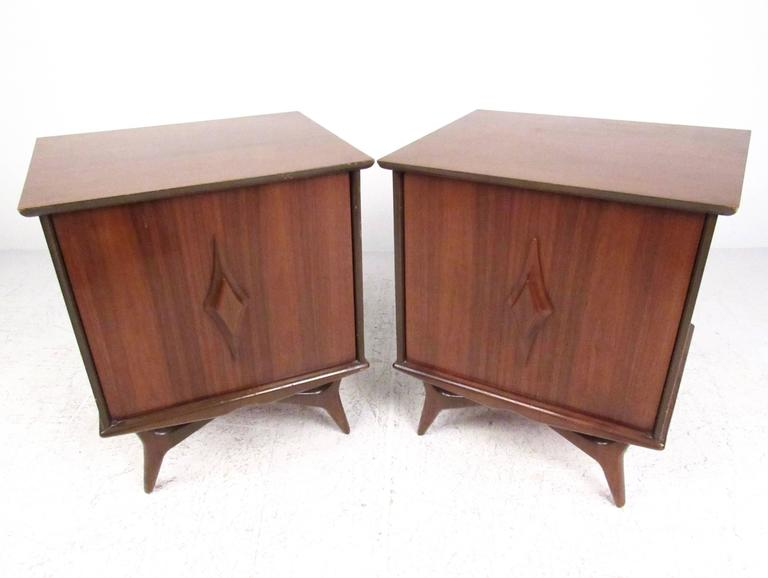 This stunning pair of vintage walnut nightstands features sculpted door fronts, tapered legs, and spacious interior cabinets. Adjustable shelves make this matching pair the perfect addition to bedroom or living room, allowing for stylish end table