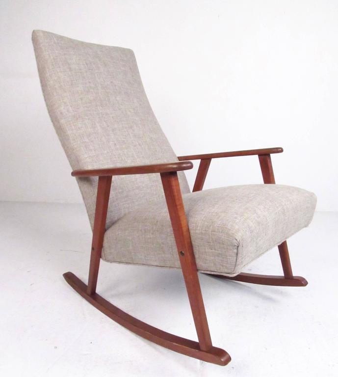 This stylish Scandinavian Modern rocking chair features a well-crafted teak frame and upholstered high back seat. Simple elegance combines mid-century design with timeless comfort, making this the perfect rocker for any setting. Please confirm item