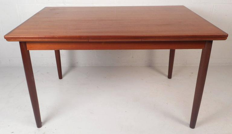 """This beautiful vintage modern dining table features two hidden leaves that draw out to make this table an impressive 93.25"""" wide. Elegant teak wood grain and tapered legs add to the allure. This versatile design is sure to make a lasting"""