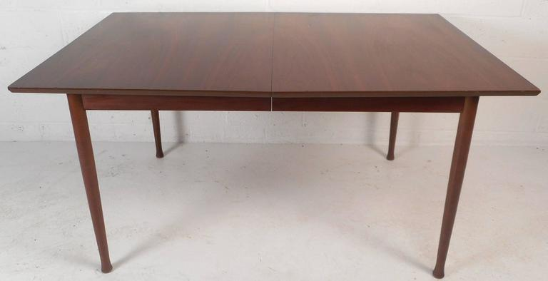 This beautiful vintage modern dining table has rosewood accents along the edges of two sides. Stylish design with unique drum stick legs and elegant wood grain. Sturdy construction with stunning features makes the perfect addition to any modern