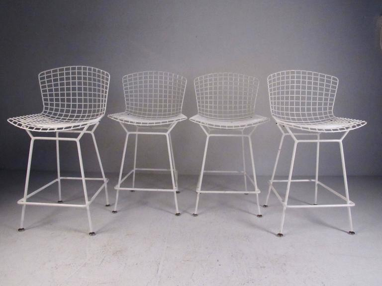 This stylish set of four Mid-Century bar stools as designed by Harry Bertoia for Knoll International, circa 1970s. Stunning modern design includes sculpted wire seat and sturdy footrest. Please confirm item location (NY or NJ).