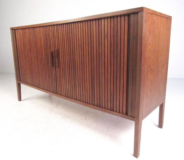 This stylish Mid-Century credenza makes a unique storage piece perfect for use as a television console, storage cabinet, or for occasional service. Walnut construction with tambour door and spacious shelf storage make this ideal for home or office.