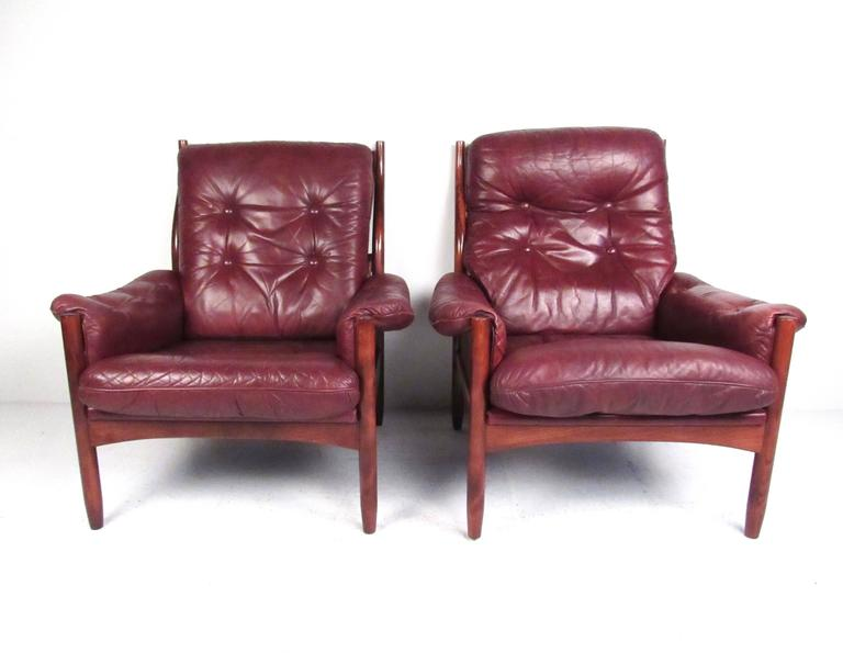 This beautiful pair Scandinavian Modern lounge chairs features tufted vintage leather, sleek and slender rosewood frame, and unique Danish design. The comfortable and stylish contour of the seat back adds to the mid-century appeal of the pair.