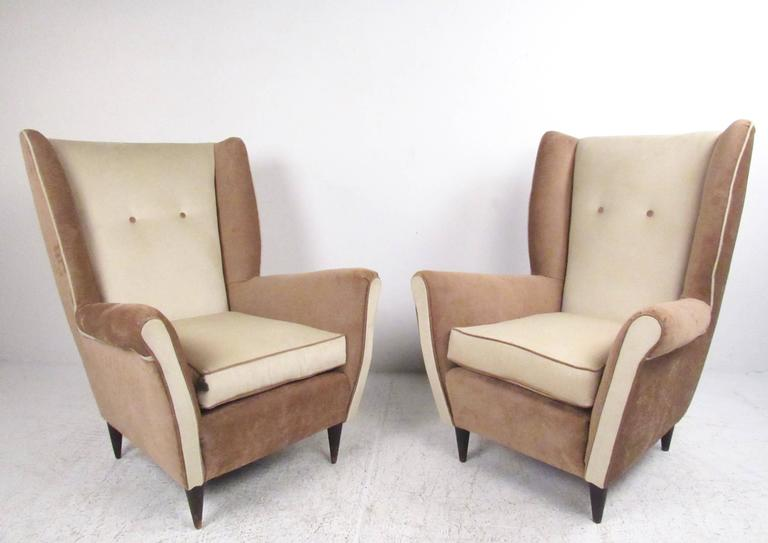This stylish pair of Mid-Century lounge chairs feature high sculpted seat backs, comfortable and accommodating seats and tapered hardwood legs. Exquisite two tone fabric is complimented by trim piping and button tufted seat backs. Perfect pair of