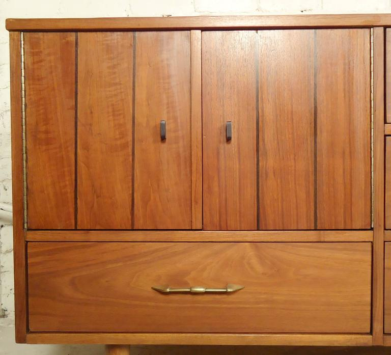 American vintage dresser with warm walnut grain. Long credenza style with four drawers and side cabinet. Accenting brass handles.