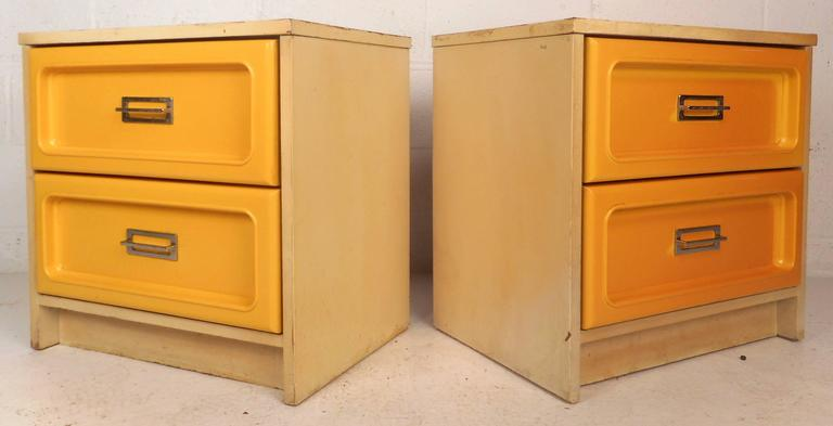 This beautiful vintage modern bedroom set features two nightstands and a dresser. The stylish design has laminate around the sides and top with unique yellow drawer fronts. Each drawer has unique chrome pulls with a recessed rectangle design.