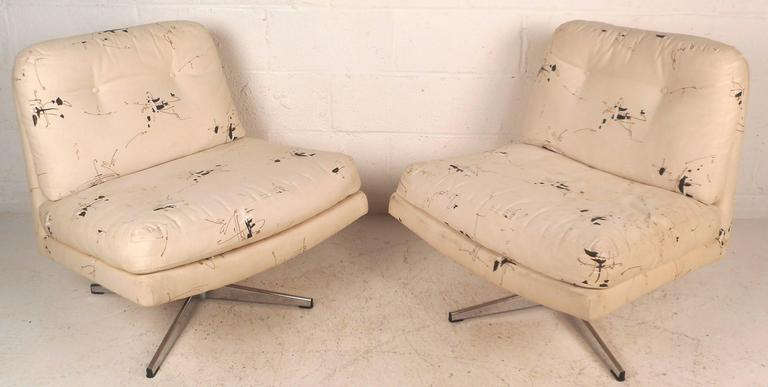 This gorgeous pair of vintage modern lounge chairs feature a slipper design with wide seating and the ability to swivel. Thick padded cushions and original tufted upholstery add to the allure. Unique mid-century pair of lounge chairs ensure comfort