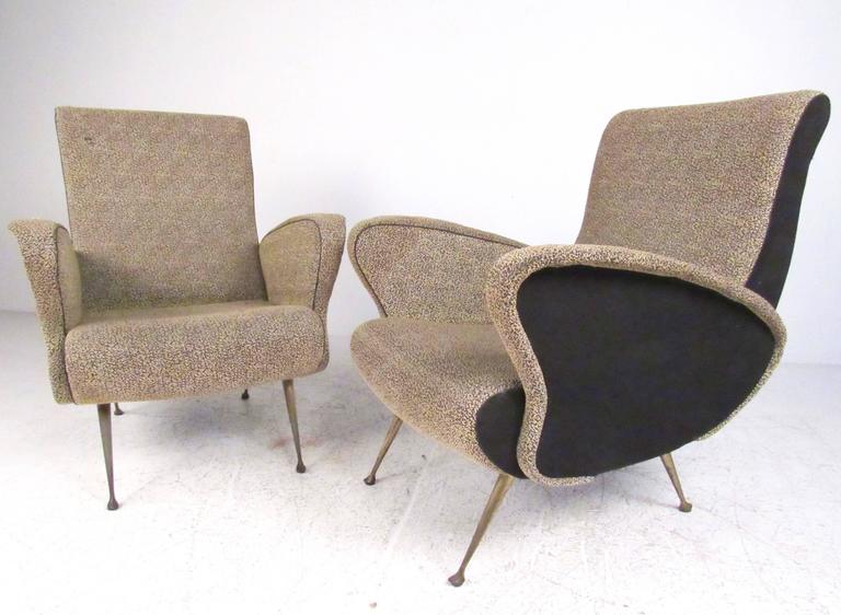 This stylish pair of Italian modern lounge chairs feature sculpted frames with vintage upholstery and unique tapered brass legs. Two-tone fabric adds to the stylish lines of this Gio Ponti style armchairs. Please confirm item location (NY or NJ).